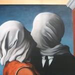 Dos personas se besan mientras su cabezas son cubiertas por una sábana blanca.